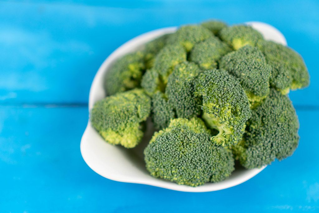Fresh Broccoli in the bowl above blue wooden table