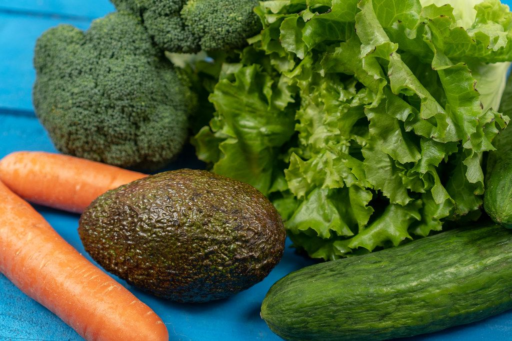 Fresh Carrots, Avocado, Broccoli, Lettuce and Cucumber on the blue boards