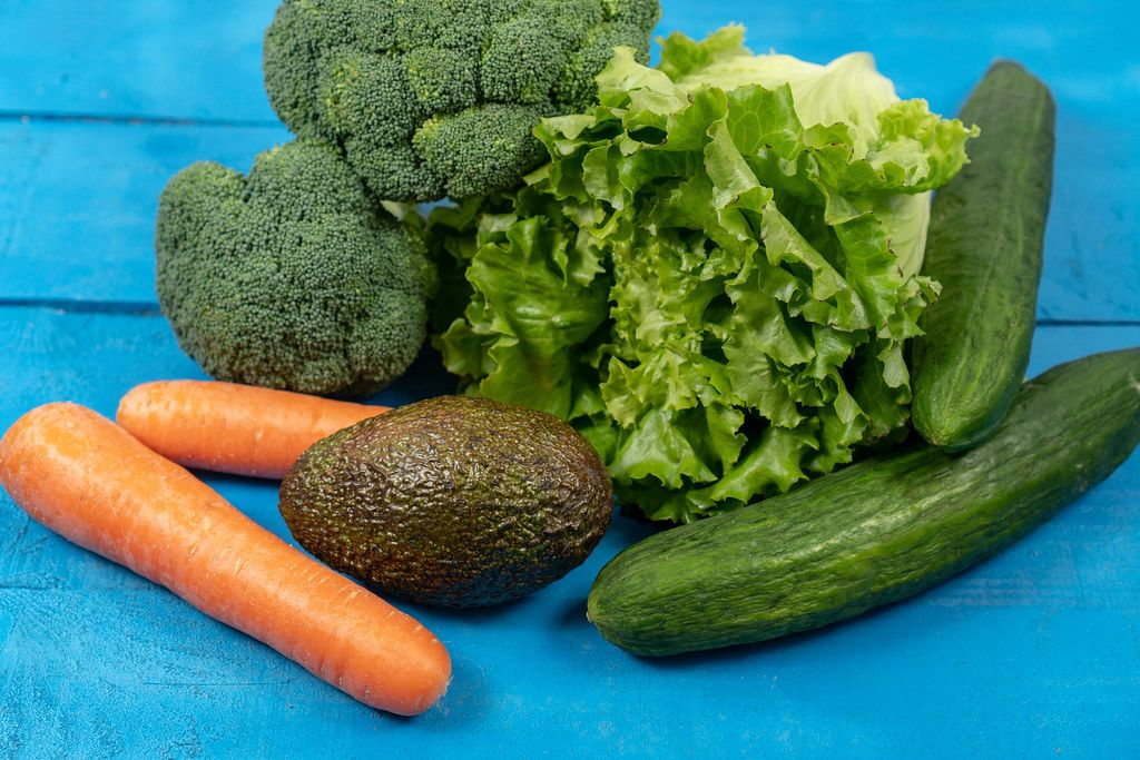 Fresh Carrots, Avocado, Broccoli, Lettuce and Cucumber on the wooden table