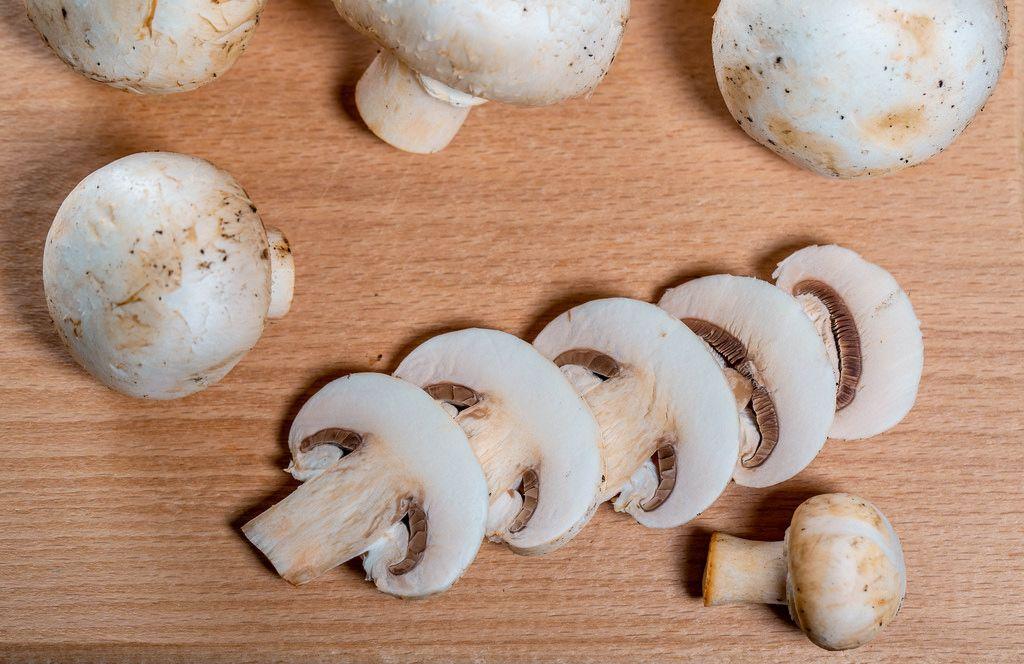 Fresh champignon mushrooms on wooden background.