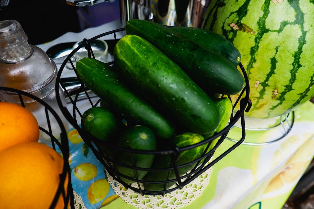 Fresh cucumber on black metal basket