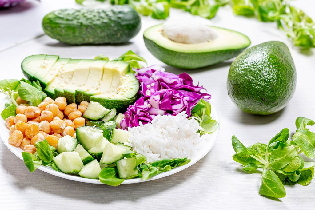 Fresh cucumbers, avocado, purple cabbage, corn salad with rice and chickpeas