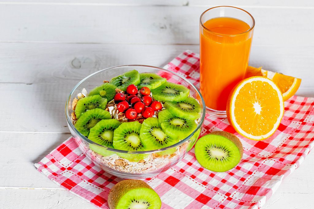 Fresh fruit orange and kiwi, a glass of juice and a plate of oatmeal on a checkered dish towel