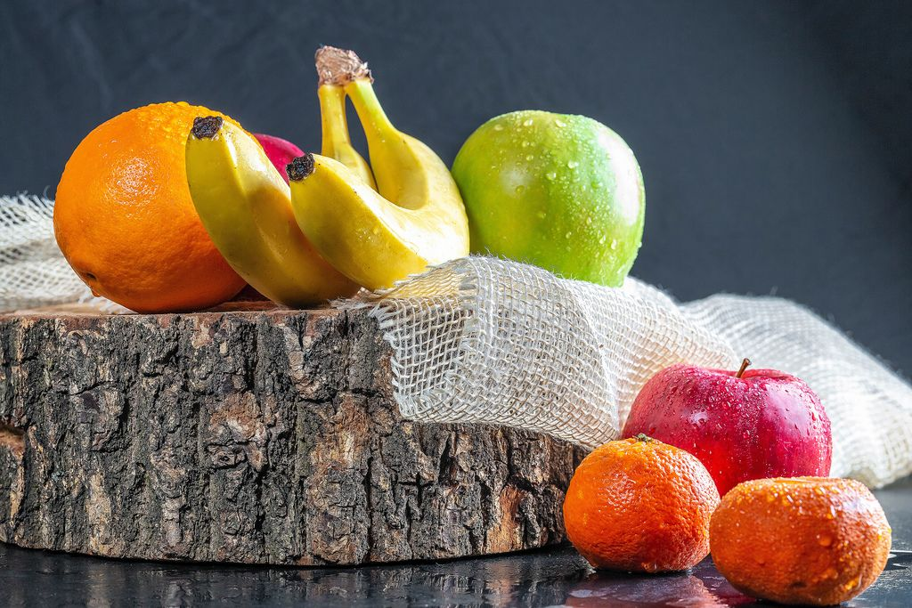 Fresh fruit with wooden stump and burlap on black table (Flip 2019)