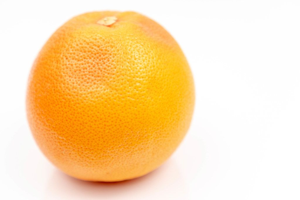 Fresh Grapefruit on the white reflective surface with copy space (Flip 2020)