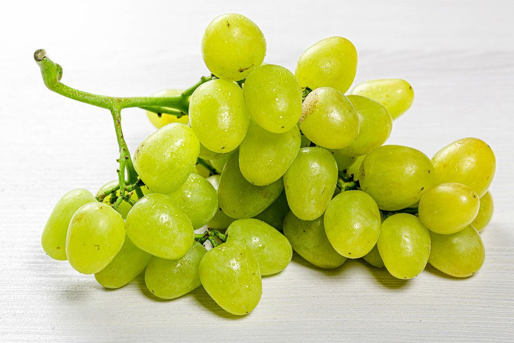 Fresh green grapes on white wooden background