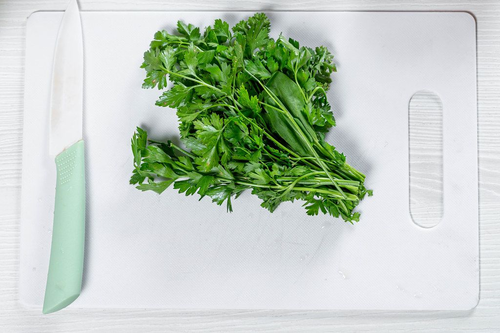 Fresh green parsley with a ceramic knife on a white kitchen Board (Flip 2019)
