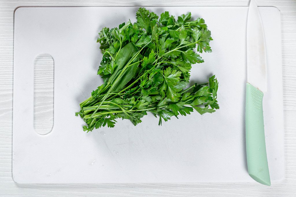 Fresh green parsley with a ceramic knife on a white kitchen Board