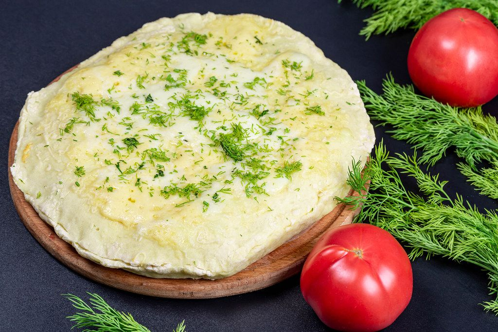 Fresh homemade khachapuri with cheese and minced meat on a black background with dill and tomatoes