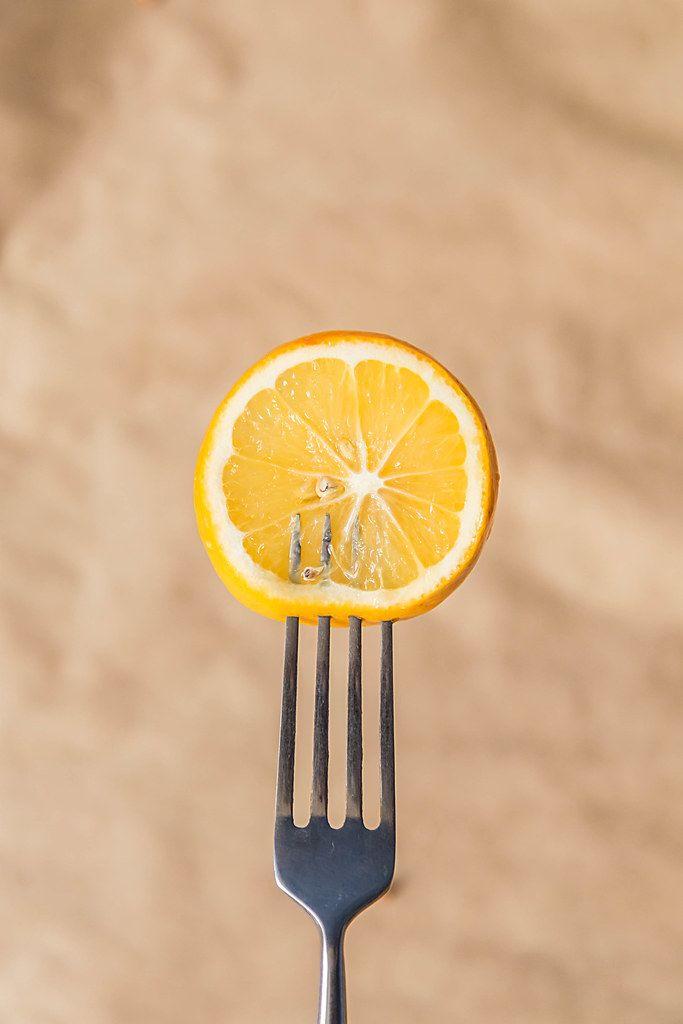 Fresh lemon slice on a fork against brown paper background (Flip 2019)
