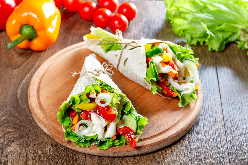 Fresh multi-colored sliced vegetables wrapped in pita bread on the kitchen Board (Flip 2019)