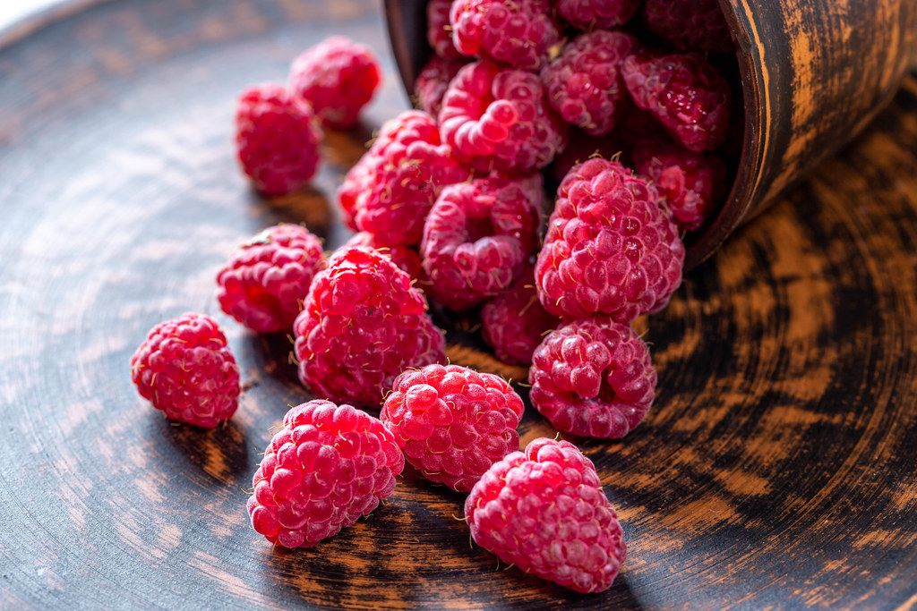 Fresh pink raspberries scattered on a brown background