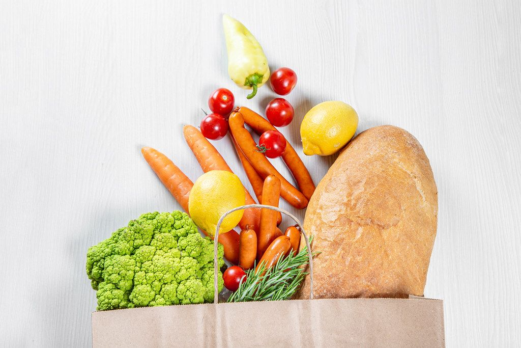 Fresh produce in paper grocery bag on white table