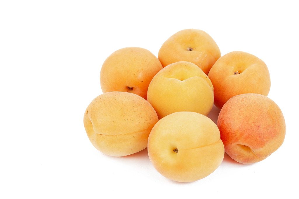Fresh raw Apricots isolated above white background
