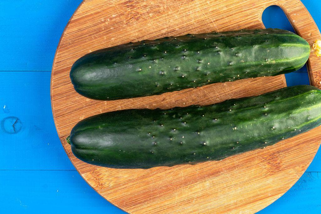 Fresh Raw Cucumber on the kitchen wooden board