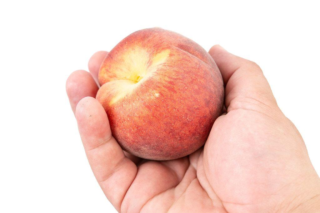 Fresh Raw Peach in the hand above white background (Flip 2019)