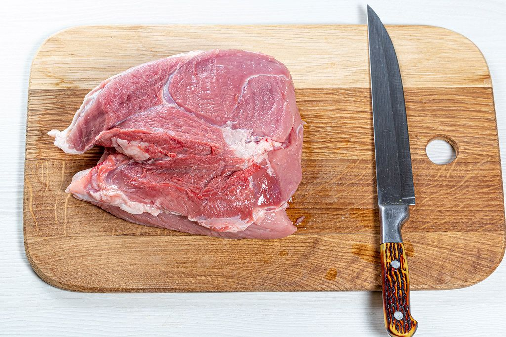 Fresh raw pork meat on kitchen board with knife