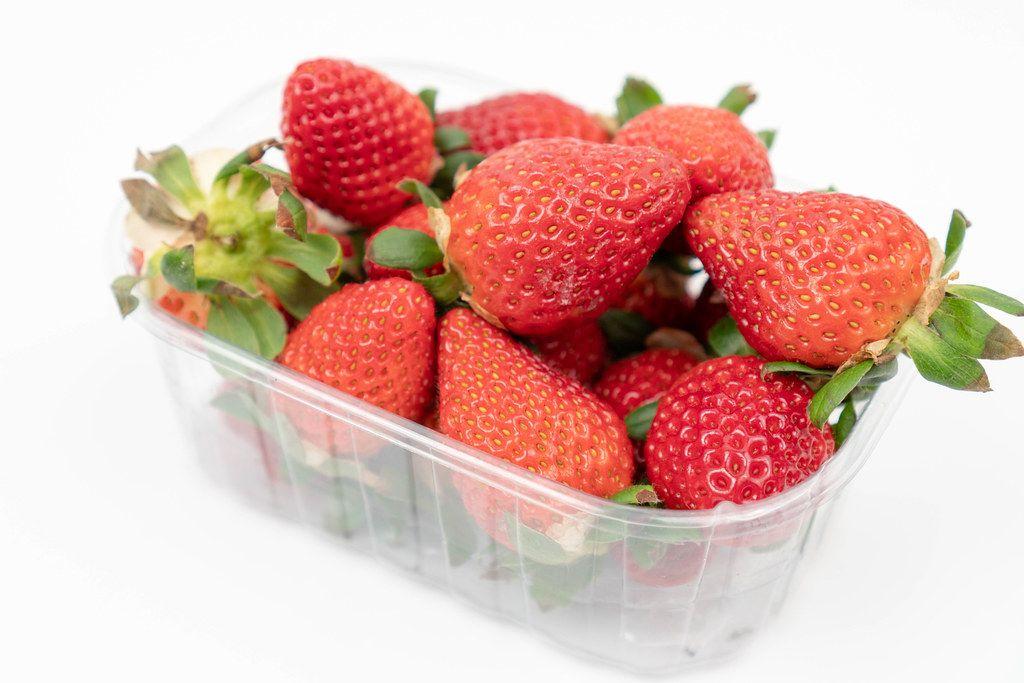 Fresh Raw Strawberries in the plastic box above white background
