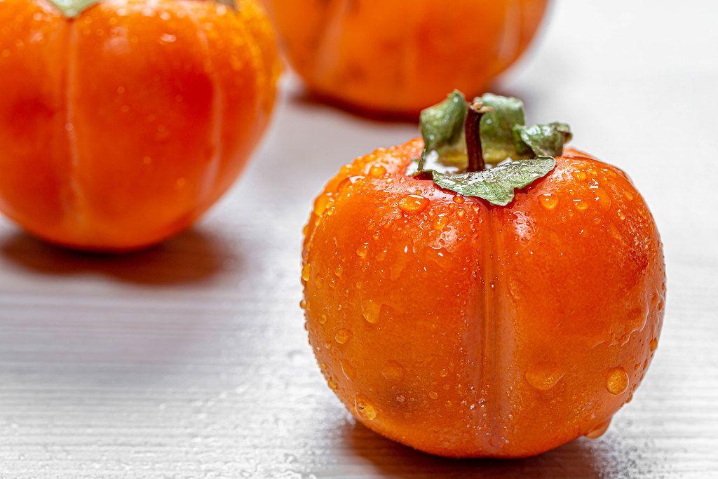Fresh ripe orange persimmons with water drops (Flip 2019)