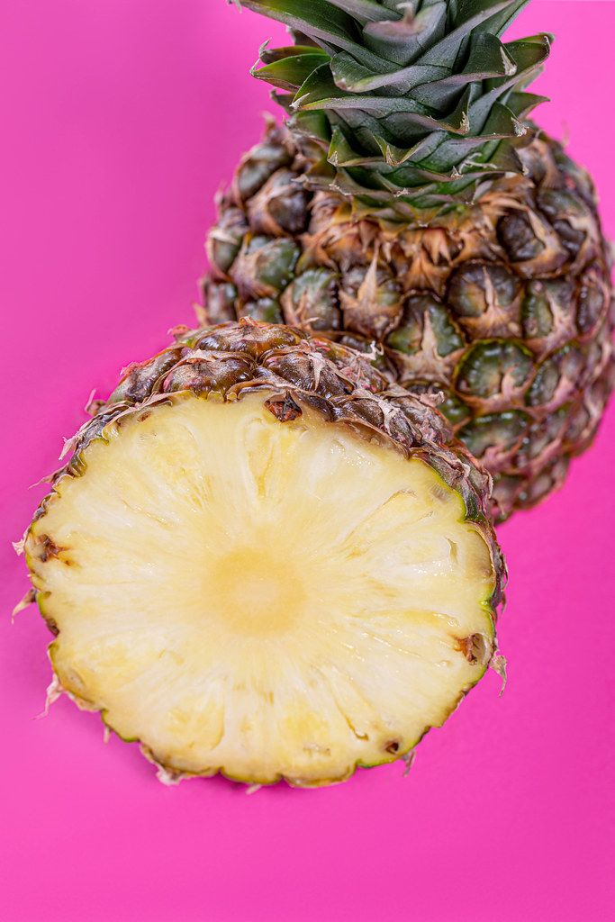 Fresh ripe pineapple halves on pink background