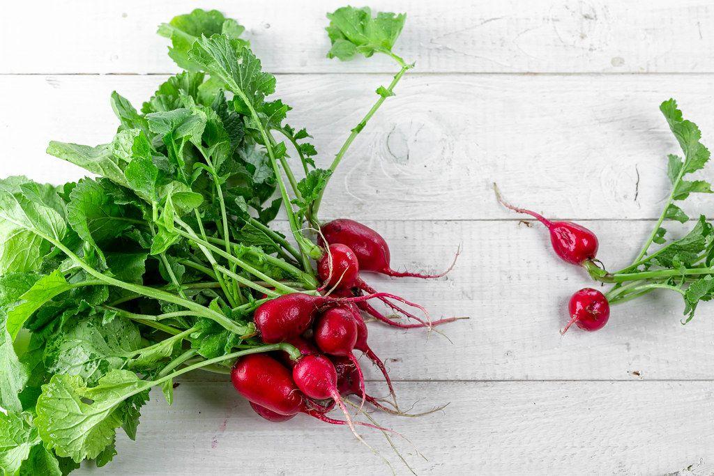 Fresh ripe radish on white wooden background