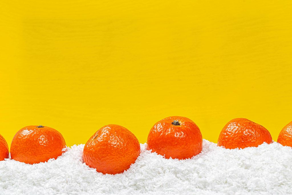 Fresh ripe tangerines on snow with yellow background behind with free space