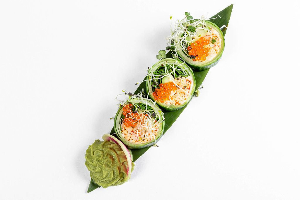 Fresh rolls with cucumber, avocado, crab, arugula and micro-greens on a large green leaf. Top view