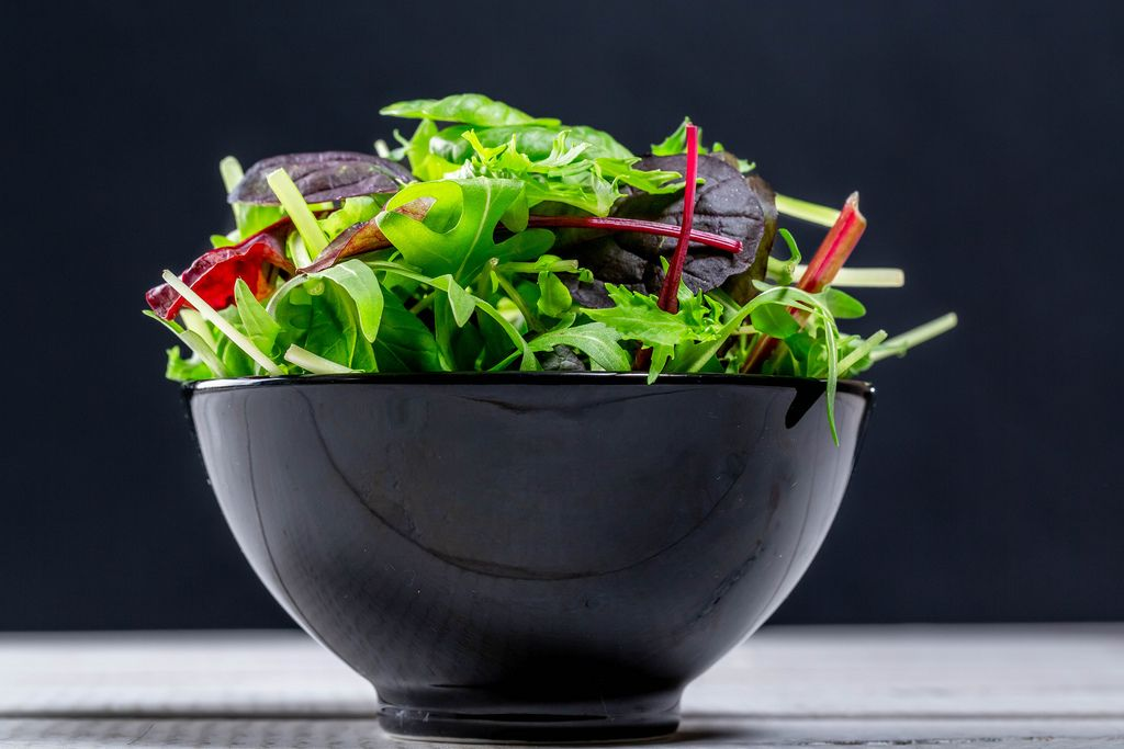 Fresh salad with a mixture of different lettuce and arugula in a black bowl