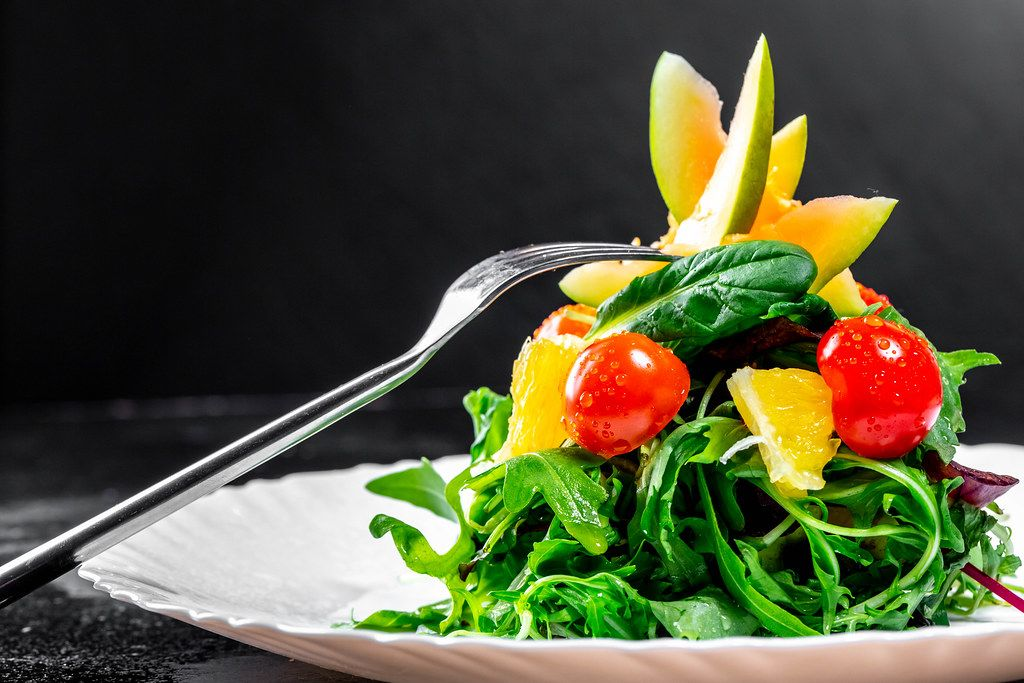 Fresh salad with herbs, tomatoes, avocado and orange on a plate with a fork (Flip 2019)