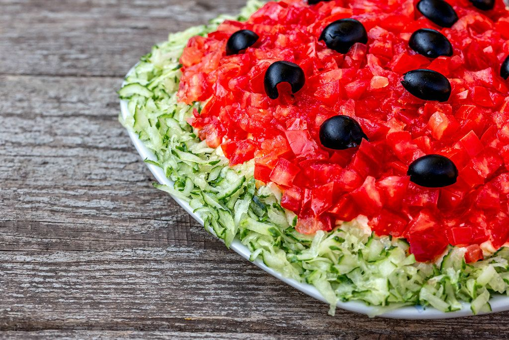 Fresh salad with tomatoes, cucumbers and black olives close-up