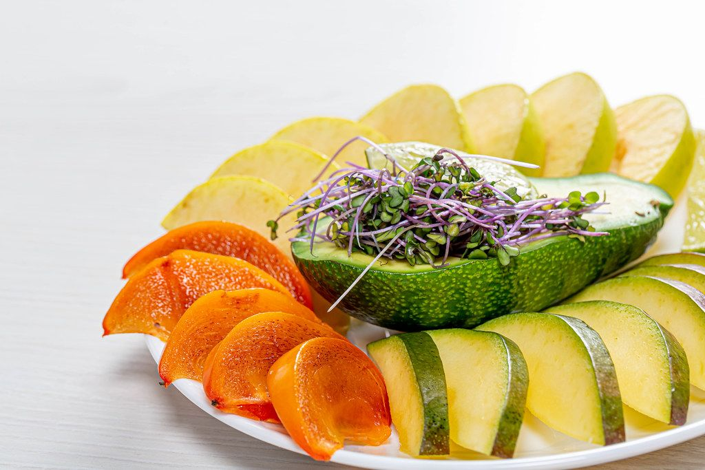 Fresh slices of mango, persimmon, Apple, lime and avocado with micro greens