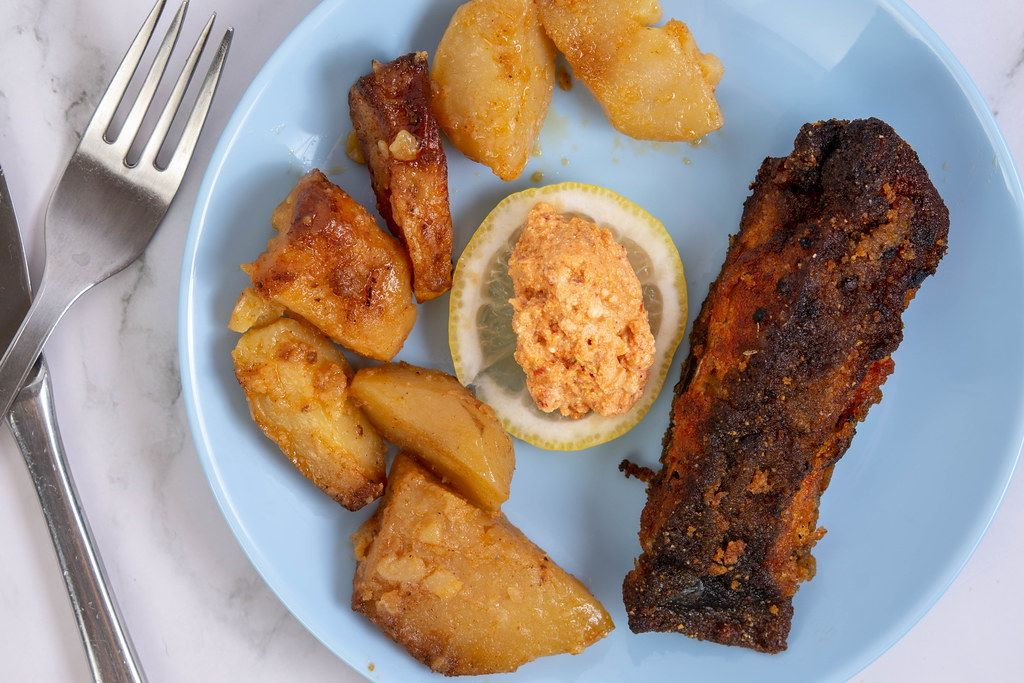 Fried Carp fish served with Potatoes and Salad on the plate