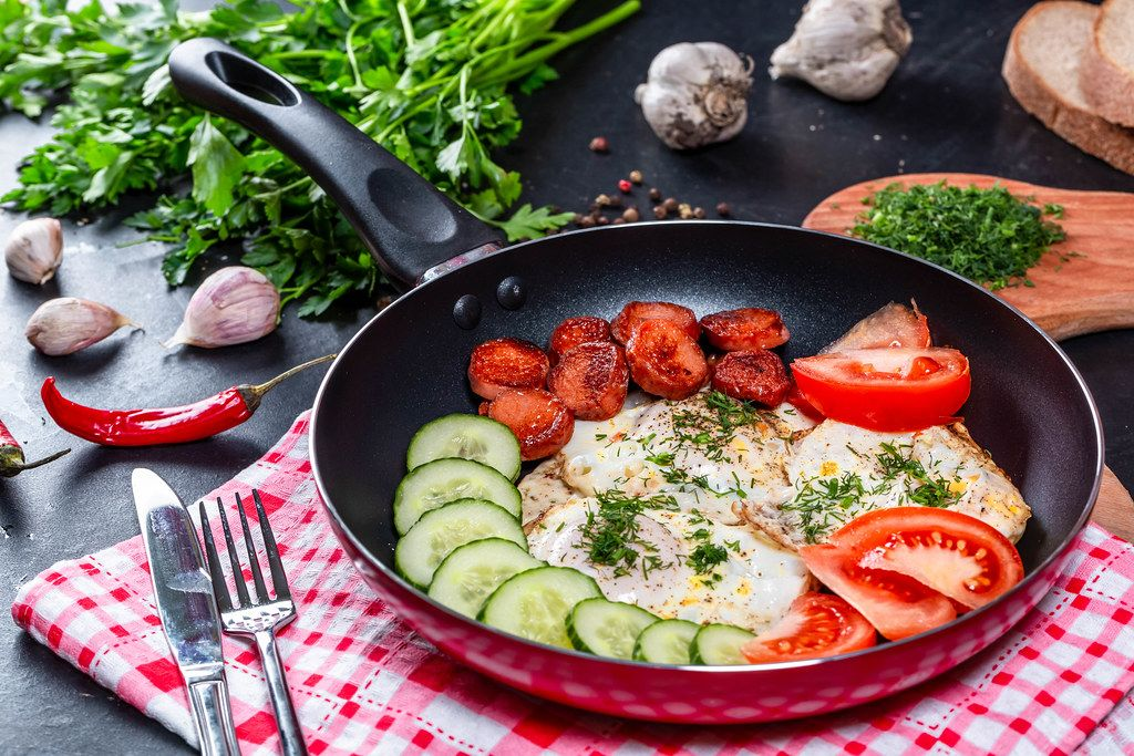 Fried eggs with vegetables and sausages in a frying pan with a knife and fork