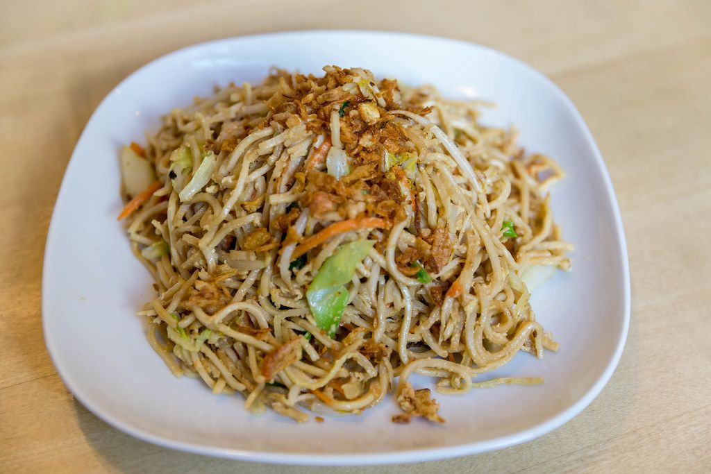Fried noodles with egg and fresh vegetables as vegetarian lunch at the Asian restaurant