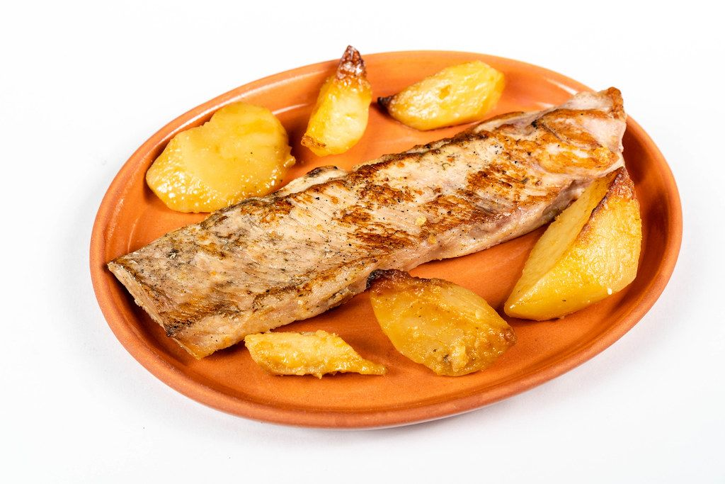 Fried Pork Steak and Potatoes isolated on a clay plate