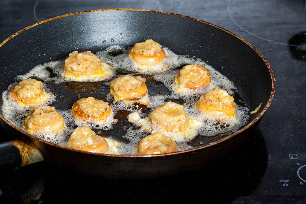 Fried stuffed bagels in a frying pan on an electric hob