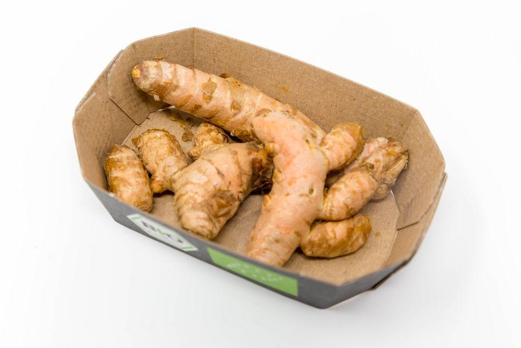 Frische Bio Kurkuma Wurzeln in einer Pappschale