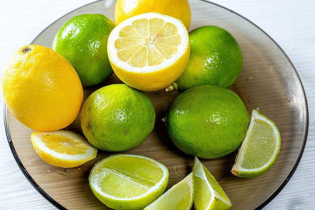 Frische Limonen, Limettenscheiben und halbierte Zitronen auf einem Glasteller