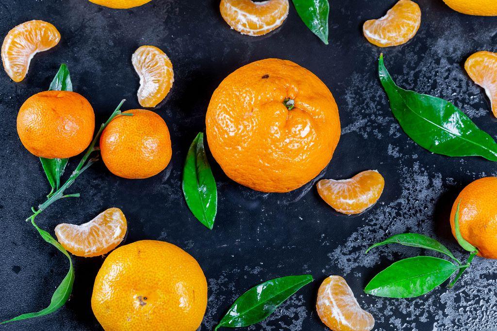 Frische Mandarinen mit Blättern und Stücken auf schwarzem Hintergrund