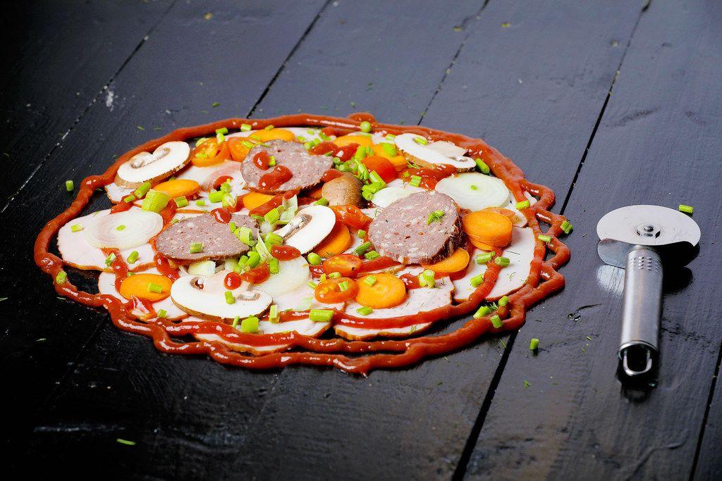 Frische Pizzazutaten neben einem Pizzamesser auf einem schwarzen Holztisch