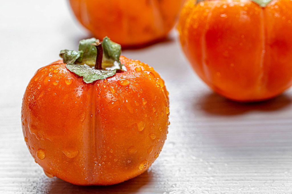 Frische, reife, orangene Persimonen mit Wassertropfen auf der Haut