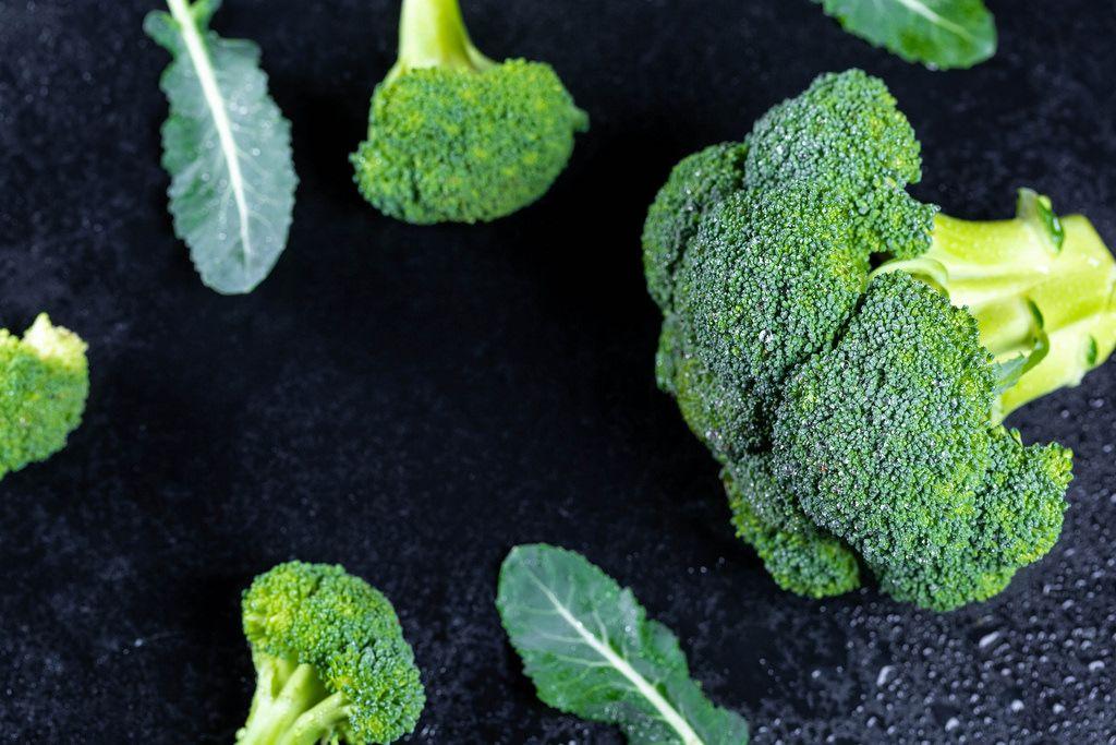 Frischer Broccoli auf schwarzem Hintergrund mit Wassertropfen