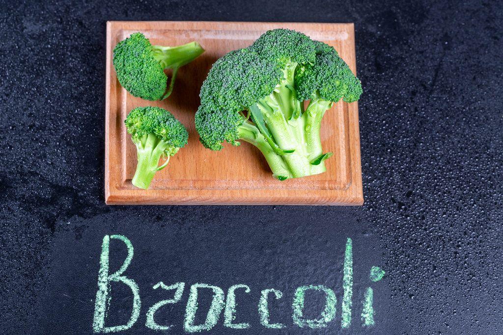 Frischer Broccoli mit Wassertropfen auf einem Küchenbrett und der Schrift Broccoli auf schwarzem Hintergrund