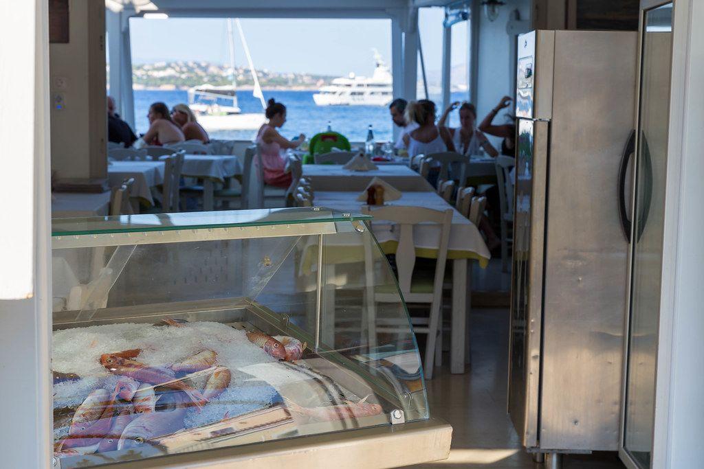 Frischer Fisch auf Eis in einer Kühltruhe, mit Restaurantbesuchern am Fensterplatz mit Meerblick