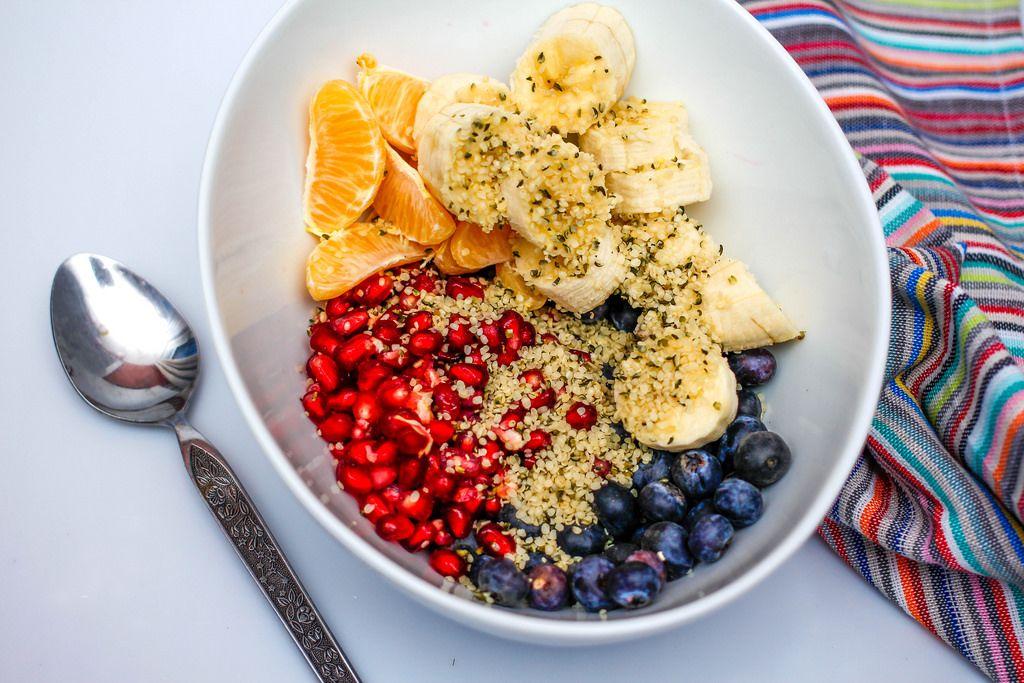 Frischer Fruchtsalat mit Banane, Orange, Blaubeeren, Granatapfel, Hanfsamen