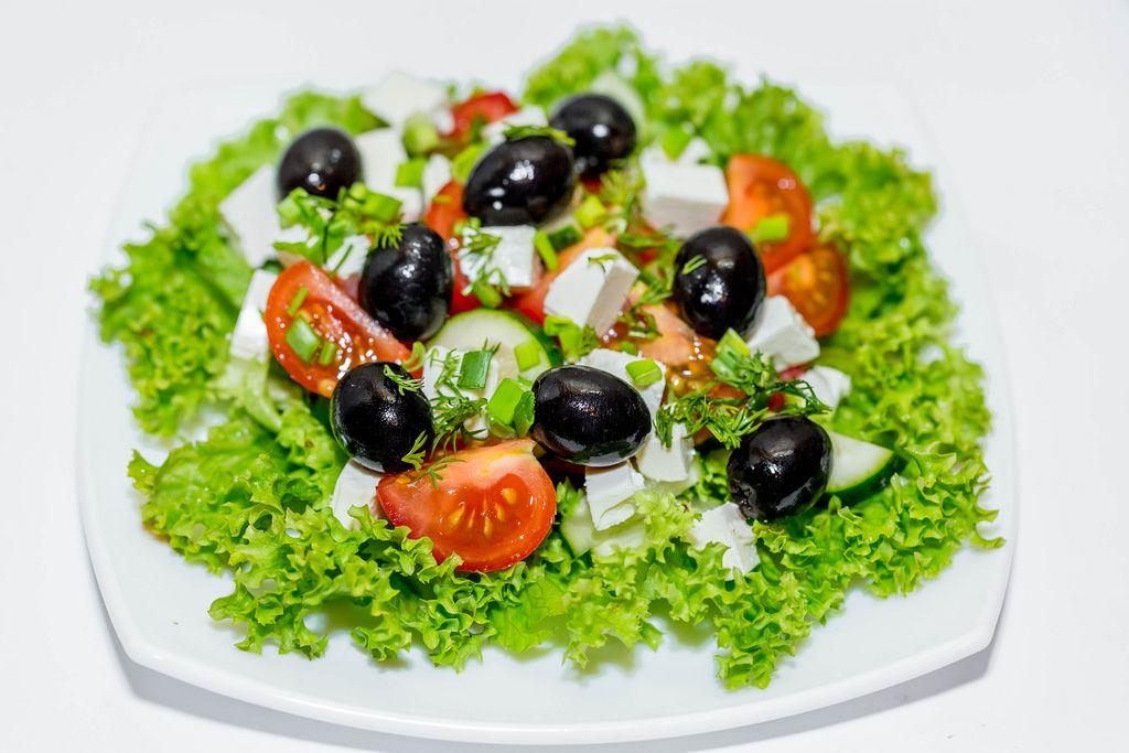 Frischer griechischer Salat bestehend aus grünen Blättern, schwarzen Oliven, Tomaten und Fetakäse