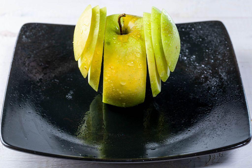 Frischer, grüner Apfel in Scheiben geschnitten auf einem schwarzen Teller mit Reflektion