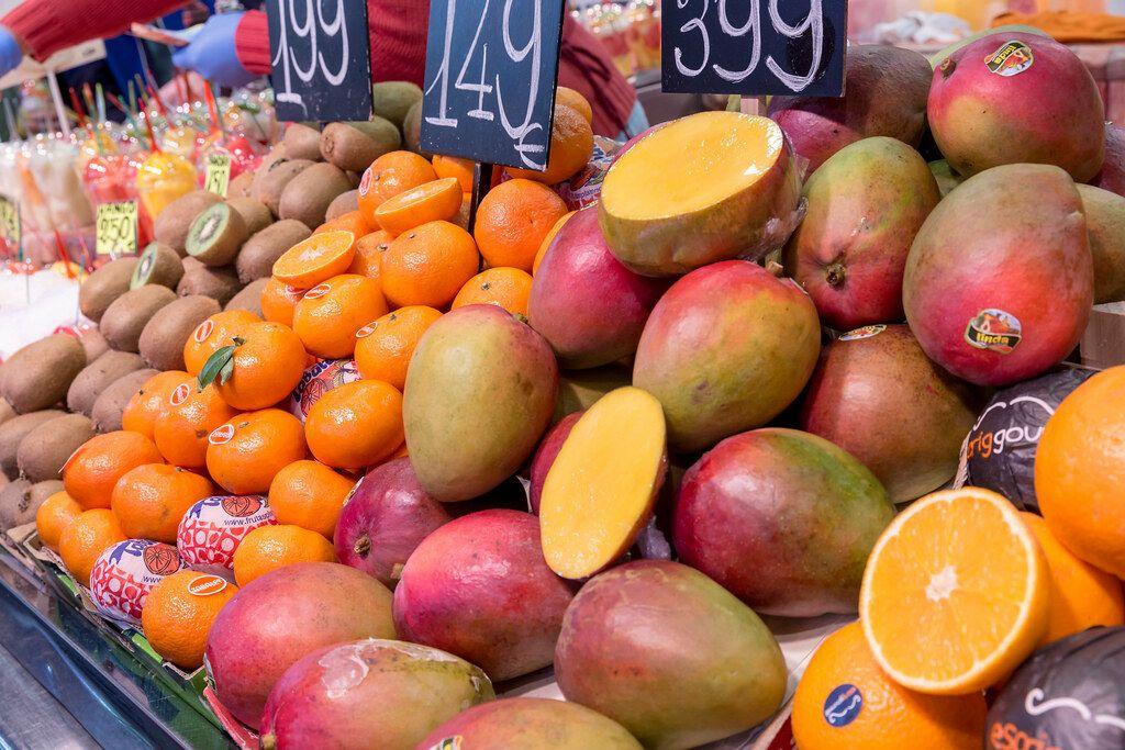 Frischer Obststand mit Mangos, Orangen und Kiwis in der Markthalle Mercat de la Boquerìa am Placa de Sant Josep in Barcelona, Spanien