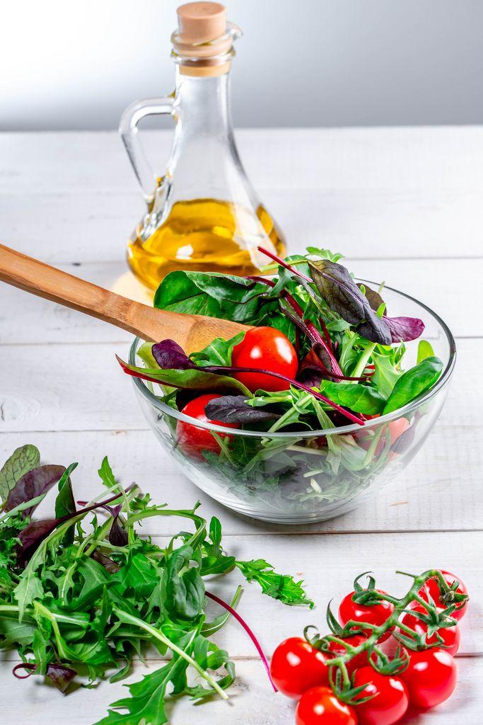 Frischer Salat-Mix mit Rucola, Spinatblätter, Tomatenstaude und Olivenöl auf einem weißen Holztisch