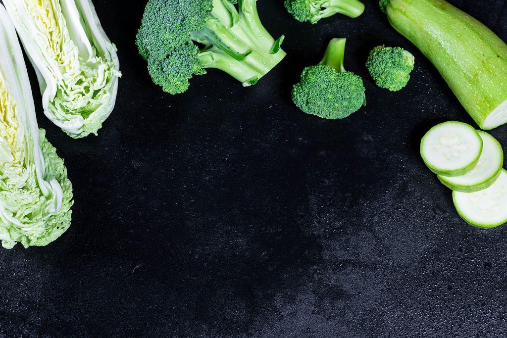 Frisches Gemüse, Kohl, Zucchini und Broccoli mit Wassertropfen auf schwarzem Hintergrund